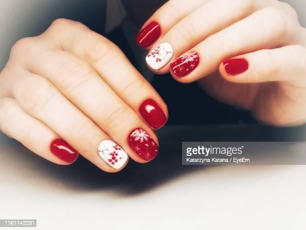 close-up of woman wearing red nail polish on fingernails - red nail polish stock pictures, royalty-free photos & images