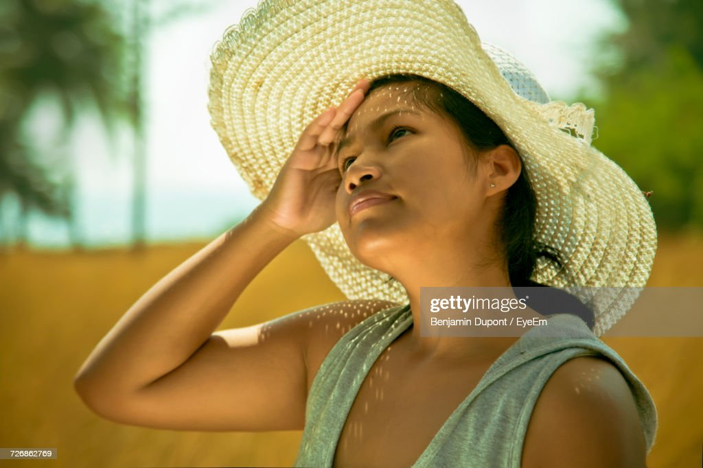 9152f3034 Closeup Of Woman Wearing Sun Hat While Looking Up On Sunny Day Stock ...