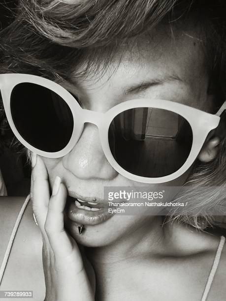 Close-Up Of Woman Wearing Sunglasses With Hand On Chin