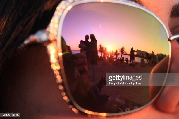 Close-Up Of Woman Wearing Sunglasses With Reflection Of People At Beach