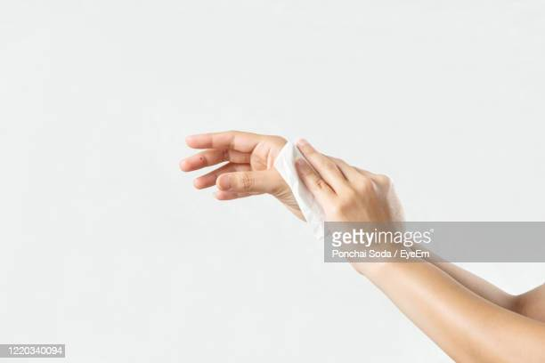 close-up of woman wiping hands with tissue against white background - wet wipe stock pictures, royalty-free photos & images