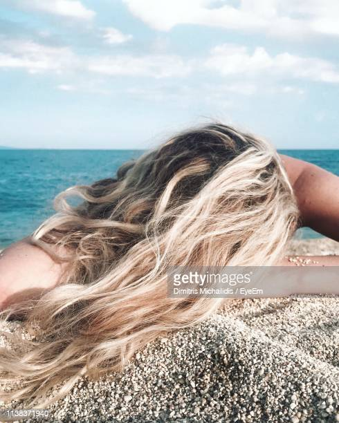 close-up of woman with blond hair lying at beach against sky - blond frauen strand stock-fotos und bilder