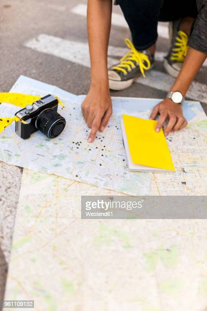 Close-up of woman with camera searching on city map