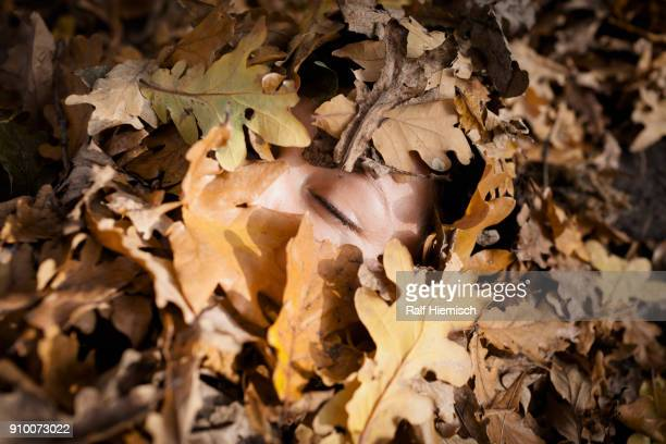 Close-up of woman with closed eyes covered in dry leaves during autumn