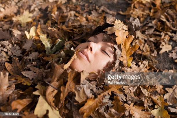Close-up of woman with closed eyes covered in dry leaves