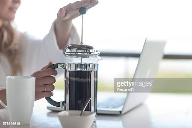 Close-up of woman with coffee plunger using laptop