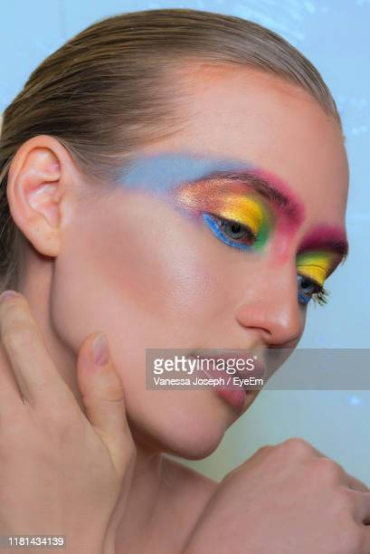 close-up of woman with colorful eye make-up - アイメイク ストックフォトと画像