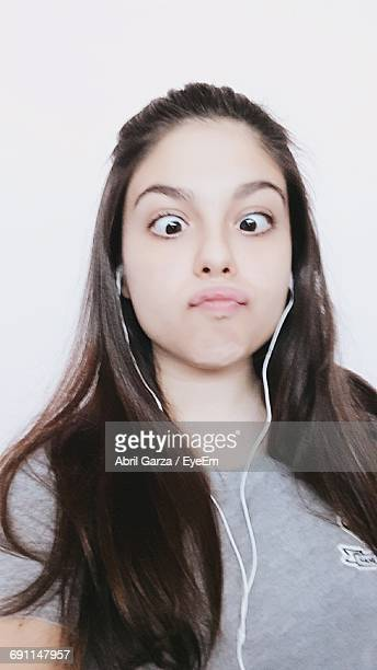 Close-Up Of Woman With Cross-Eyed Listening Music Against White Background
