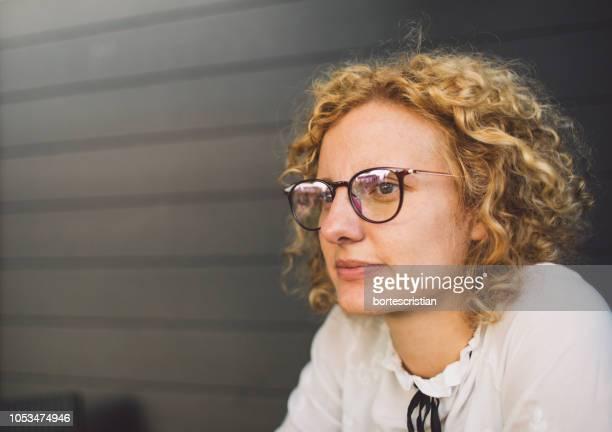 close-up of woman with curly hair looking away - bortes fotografías e imágenes de stock