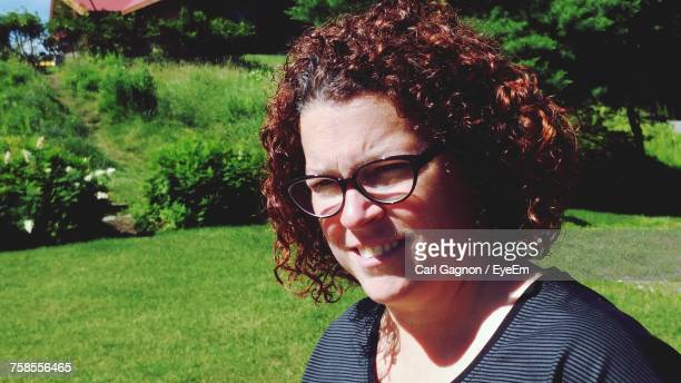Close-Up Of Woman With Curly Hair Wearing Eyeglasses On Sunny Day