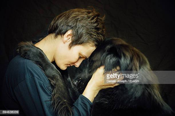 Close-Up Of Woman With Dog Against Black Background