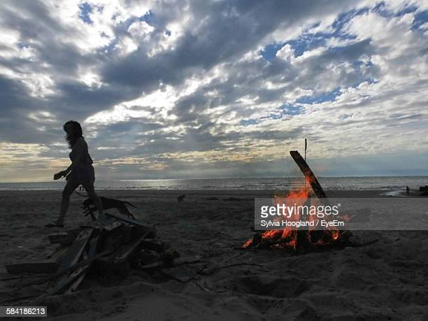 Close-Up Of Woman With Dog By Campfire At Beach Against Cloudy Sky