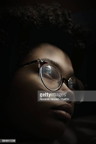 Close-Up Of Woman With Eyeglasses Against Black Background