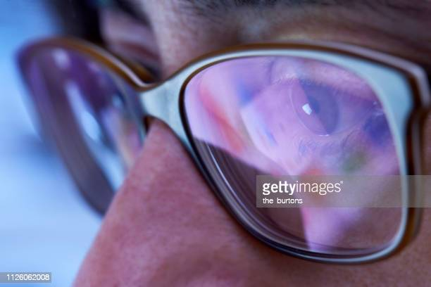 close-up of woman with eyeglasses looking to computer monitor - the eyes have it stock pictures, royalty-free photos & images