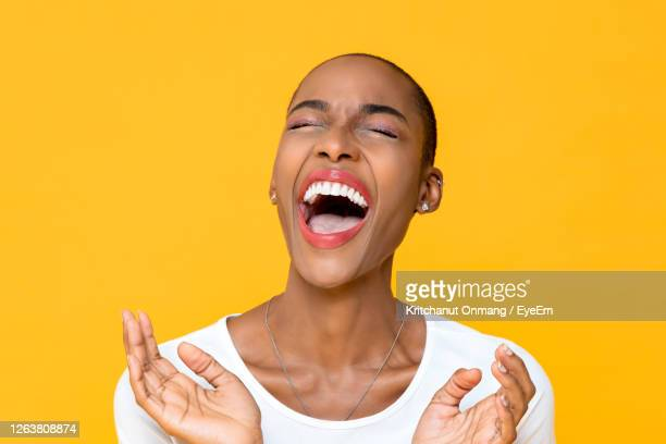 close-up of woman with eyes closed laughing against yellow background - glattrasiert frau stock-fotos und bilder
