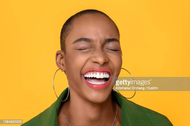 close-up of woman with eyes closed laughing against yellow background - cabeza afeitada fotografías e imágenes de stock