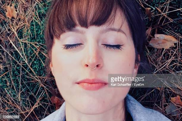 close-up of woman with eyes closed lying down on field - lying down stock-fotos und bilder
