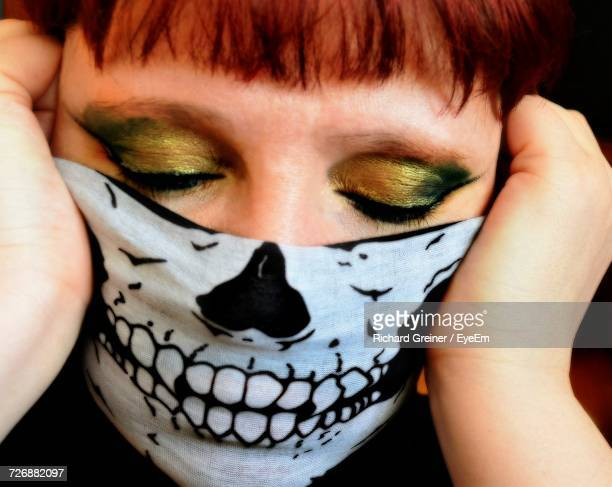 Close-Up Of Woman With Eyes Closed Wearing Skull Mask