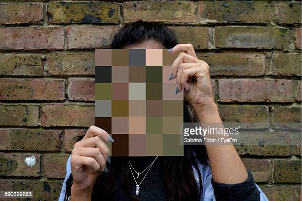 Close-Up Of Woman With Face Covered By Color Swatch Against Brick Wall