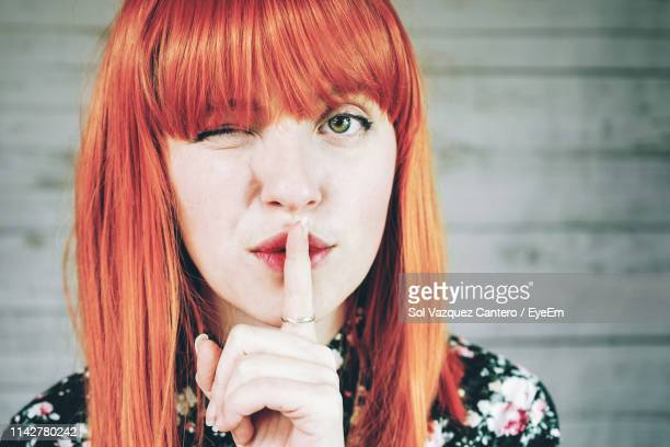 close-up of woman with finger on lips - finger on lips stock pictures, royalty-free photos & images