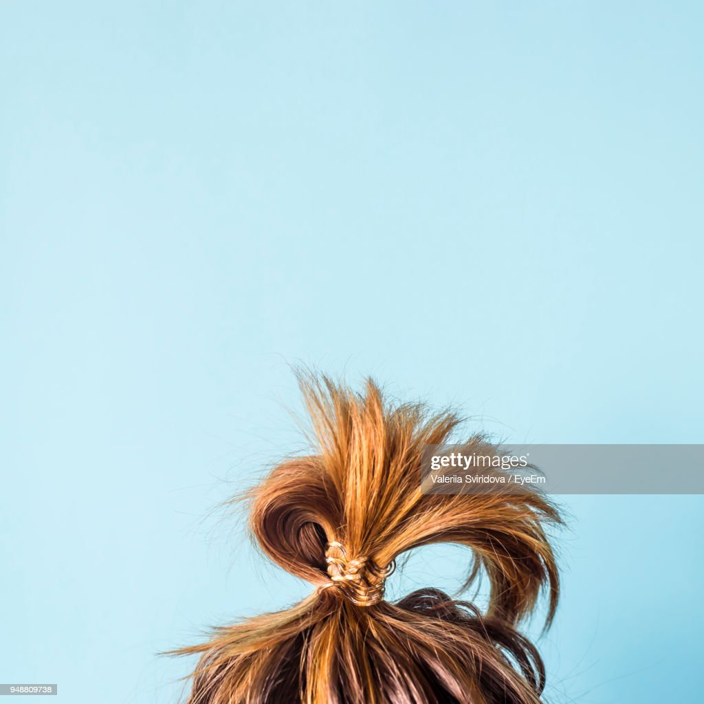 Close-Up Of Woman With Hair Bun Against Blue Background : Stock Photo