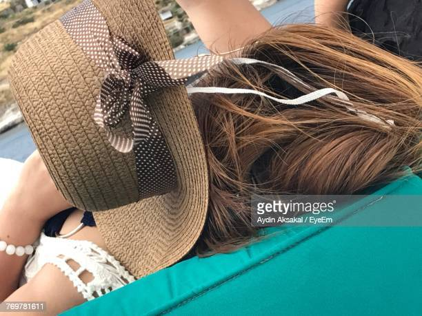 Close-Up Of Woman With Hat Lying On Sofa Outdoors