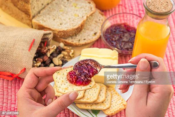 Close-Up Of Woman With Jam And Crackers