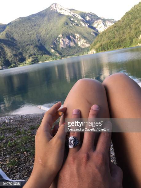 close-up of woman with man holding cigarette against lake - man touching womans leg fotografías e imágenes de stock