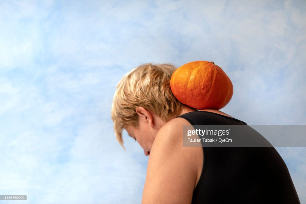 Close-Up Of Woman With Pumpkin Against Sky : ストックフォト