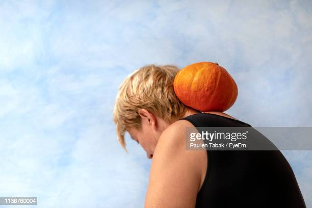 close-up of woman with pumpkin against sky - paulien tabak stock pictures, royalty-free photos & images