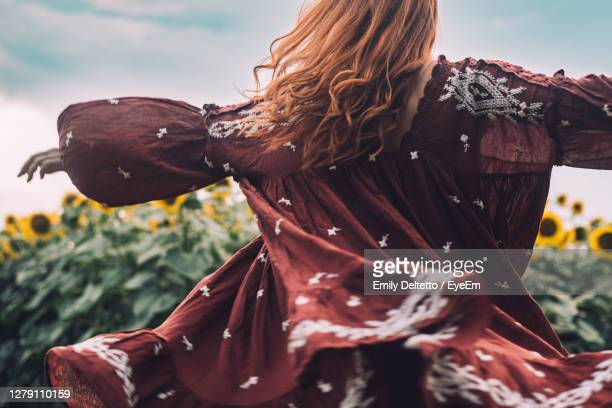 close-up of woman with red hair spinning around in a sunflowers field - dress stock pictures, royalty-free photos & images