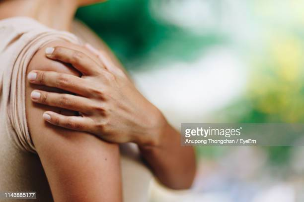 close-up of woman with shoulder pain - shoulder stock pictures, royalty-free photos & images
