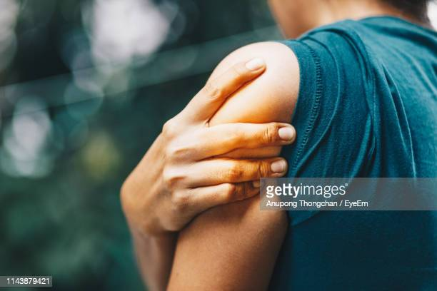 close-up of woman with shoulder pain while standing outdoors - shoulder stock pictures, royalty-free photos & images