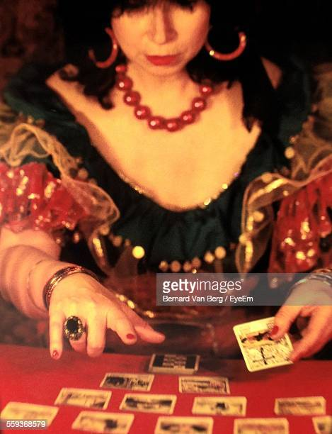 Close-Up Of Woman With Tarot Cards On Table