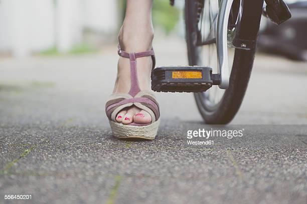 Close-up of woman with wedges on bicycle