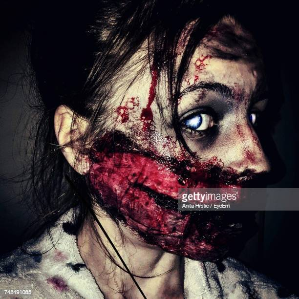close-up of woman with zombie make up during halloween in dark - zombie makeup stock photos and pictures