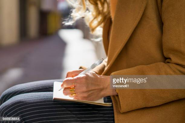 close-up of woman writing in notebook - dagboek stockfoto's en -beelden