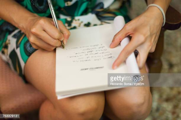 Close-Up Of Woman Writing Notes