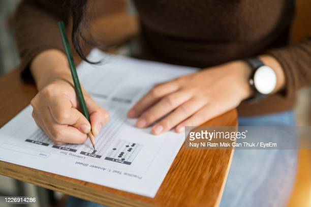 close-up of woman writing on table - college admission stock pictures, royalty-free photos & images