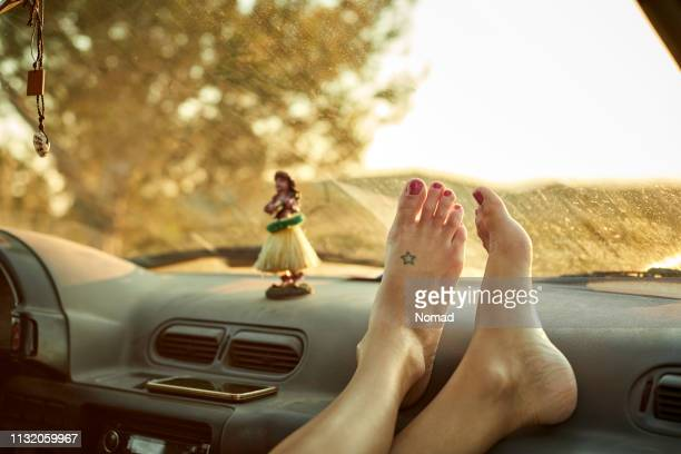 close-up of woman's feet on dashboard of mini van - hula dancer stock pictures, royalty-free photos & images