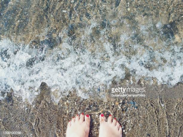 close-up of woman's feet standing in ocean surf, malaga, spain - モバイル撮影 ストックフォトと画像
