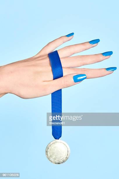 close-up of woman's hand holding a medal - medallist stock pictures, royalty-free photos & images