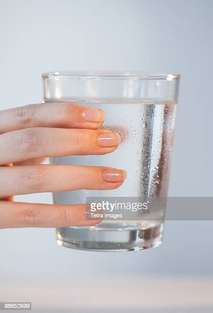 Close-up of womans hand holding glass of water