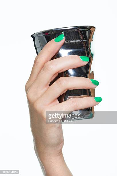 Close-up of woman's hand holding silver cup