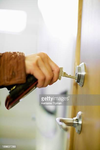 Close-up of woman's hand locking door using keys