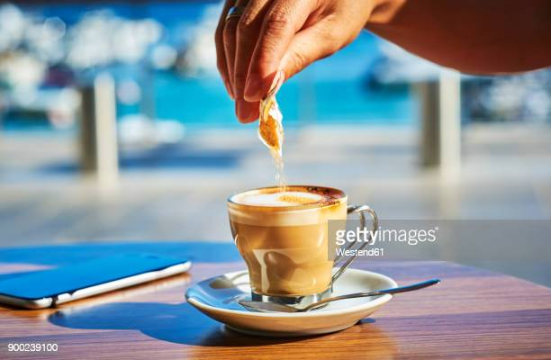 Close-up of woman's hand pouring sugar into glass of Espresso Macchiato