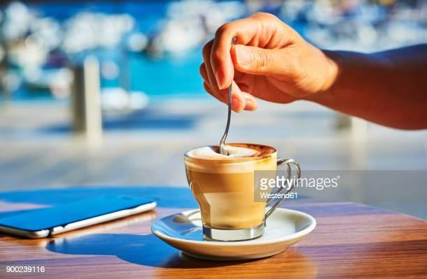 Close-up of woman's hand stirring glass of Espresso Macchiato