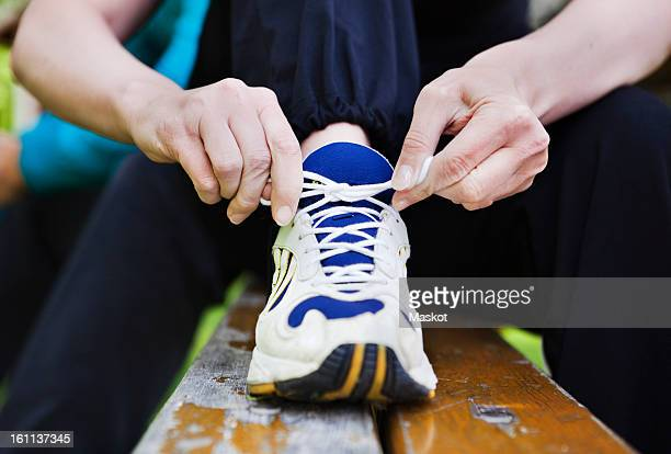 Close-up of woman's hand tying shoelace