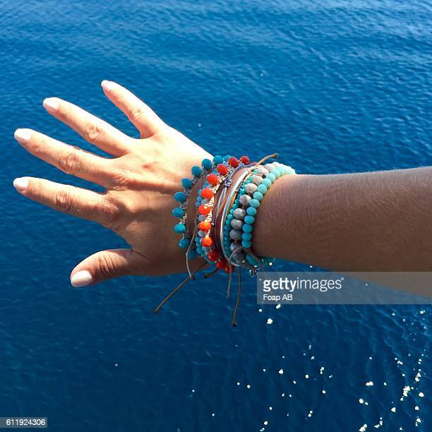Close-up of woman's hand with bracelet against blue sea