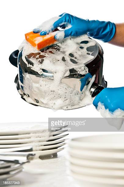 Close-up of woman's hands in protective gloves washing dishes, pots
